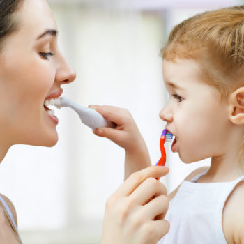 Mom and daughter brushing each others' teeth