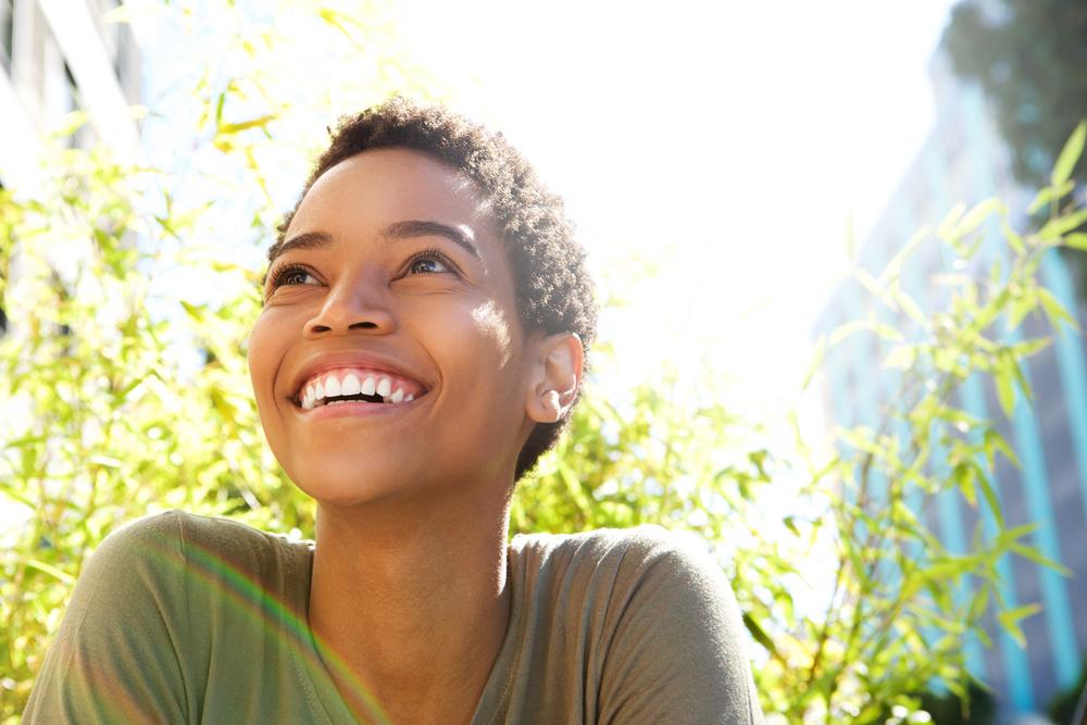 A woman smiles after her dental bonding procedure.